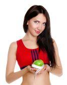 Jeune fille mince, tenant une pomme avec un ruban à mesurer — Photo