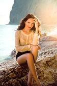 Красивая молодая девушка, сидя на пляже — Стоковое фото