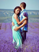 Young attractive couple in a field in summer — Stock Photo
