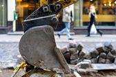 Excavator bucket on a background of street repairs — Stock Photo