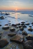 Stones in the sea froze in the ice at sunset — Stock Photo