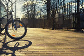 Bike with orange reflector at the fence of the park — Stock Photo