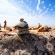 Pyramid of the old stones on the beach with the sun vacationers — Stock Photo #68702503