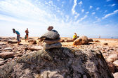 Pyramid of the old stones on the beach with the sun vacationers  — Stock Photo