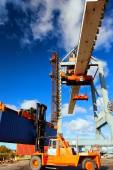 Orange forklift and crane at loading and unloading of cargo in t — Stock Photo