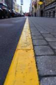 Gele lijn tussen de stoep en de weg in de stad — Stockfoto