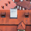 Red tiled roofs of different buildings in Prague — Stock Photo #72323299