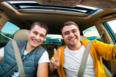 Happy friends ready for vacations driving car — Stock Photo