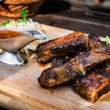Pork ribs with sauce and salad on wooden desk at the restaurant — Stock Photo #56426781