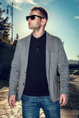 Young stylish sexy handsome model man in casual cloth lifestyle in the street in glasses — Stock Photo