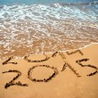 New Year 2015 is coming concept - inscription 2014 and 2015 on a beach sand, the wave is covering digits 2014 — Stockfoto #59316065