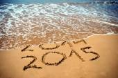 New Year 2015 is coming concept - inscription 2014 and 2015 on a beach sand, the wave is covering digits 2014 — Stockfoto
