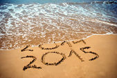 New Year 2015 is coming concept - inscription 2014 and 2015 on a beach sand, the wave is covering digits 2014 — Stok fotoğraf