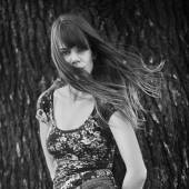 Black and white photo of woman posing near a tree with windy hair — Stock Photo