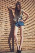 Beautiful young brunette in jeans clothes posing outdoor near red brick wall — Stock Photo