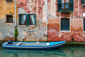 Venice cityscape, boat on narrow water canal near colorful wall with window — Stock Photo