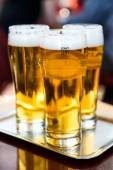 Three glasses of beer on the silver tray — ストック写真