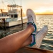 Woman legs over the sea bay and yachts at sunset time. Relaxing after runnig. — Stock Photo #76619703