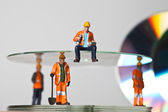 Miniature workers with CDs — Stock Photo
