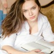 Closeup portrait of charming young sweet brunette woman beautiful girl in white shirt lying on bed reading interesting or boring book & looking at camera sensually picture — Stock Photo #52216277