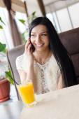 Closeup portrait of beautiful brunette young woman having fun sitting in cafe drinking orange juice happy smiling talking on mobile phone & looking at window — Stock Photo