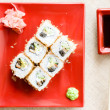 Image of delicious sushi wasabi and ginger on red plate with soy sauce and wooden chopsticks on white napkin table background — Stock Photo #52290885