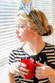 Blond contemplating beautiful young woman with red cup looking wistfully through window portrait — Stock Photo