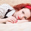 Picture of sensual red haired young woman beautiful pinup girl having fun relaxing lying in bed smiling & looking at camera closeup portrait — Stock Photo #52642535