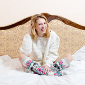 Girl in knitted sweater sitting in bed — Stock Photo