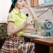 Sewing in workshop beautiful brunette young woman pinup girl with red lips and nails in yellow dress blue ribbon on her head holding cup drinking tea & looking at window closeup portrait image — Stock Photo #52669537