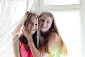 2 beautiful blond young women girlfriends having fun happy smiling hugging sitting on window & looking at camera closeup portrait picture — Stock Photo