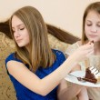 Diet & creamy chocolate cake: close up portrait of 2 beautiful young women cute blond sisters or girls friends having fun eating delicious cake together in blue and white dress & one looking away — Stock Photo #52670807