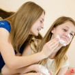 2 beautiful young women cute blond sisters or girls friends having fun together in blue and white dress smearing shaving foam laughing on the sofa close up portrait — Stock Photo #52671127