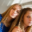 2 blond young women beautiful sisters or girl friends in blue dress having fun posing looking at camera against sun lighted rays through window blinds close up portrait image — Stock Photo #52671411