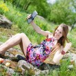 Picture of beautiful blonde woman young cute girl making selfie photo on tablet pc computer having fun happy smiling on summer green park or forest outdoors background portrait — Stock Photo #52672663