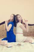 2 beautiful young women funny girls having fun celebrating happy birthday playing together in blue and white dress happy smiling & looking at camera on white bed with pink presents portrait image — Stock Photo