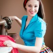 Beautiful brunette young woman pinup girl with red lips and nails in blue shirt& ribbon on her head happy smiling sewing on the machine looking at camera portrait image — Stock Photo #52936087