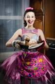 Portrait of charming sincere funny pinup girl brunette young woman in a dress apron having fun happy smiling baking tasty cake & looking at camera image — Stock Photo