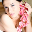 Beautiful brunette young woman blue eyes sexy girl with perfect skin having fun relaxing in spa holding pink orchid flower gently smiling & looking at camera closeup portrait image — Stock Photo #52978981