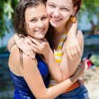 2 girls young women beautiful friends having fun happy smiling wearing wet clothes hugging & looking at camera on summer outdoor background portrait — Stock Photo #52987703