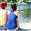 2 cute girlfriends young women in wet clothing shirts having fun relaxing sitting on the bank of the river on sandy beach ground & talking together on summer green outdoors copy space background — Stock Photo #52988315