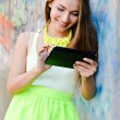 Picture of beautiful stylish fashion blond young woman reading message on tablet pc computer having fun happy smiling using internet at graffiti wall on city urban summer or spring outdoors background — Stock Photo #52989993