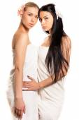 2 young beautiful women cute blond and brunette girls friends having spa procedures together in white towel, orchid in their head & looking at camera isolated on white copy space background — Stock Photo