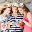 Three girlfriends typing on tablet PC — Zdjęcie stockowe #53073717