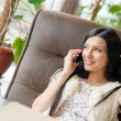 Image of beautiful brunette woman sexy girl having fun sitting in a restaurant lounge or coffee shop and talking on mobile cell phone happy smiling touching her hair & looking at copy space window — Stock Photo #53086577