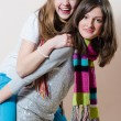 Portrait of 2 young attractive funny women having fun happy smiling & looking at camera friendly hugging & riding on one another in knitwear on light copy space background picture — Stock Photo #53088575