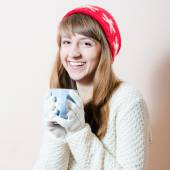 Red hat & cup: portrait of pretty girl in knitted gloves and cap with a pattern snowflakes, white sweater having fun drink beverage happy smiling & looking at camera on light copy space background — Stock Photo