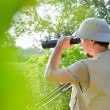 Safari tour time: picture of tourist or exploring scientist male in pith helmet having fun observing looking in magnification scope on summer sunny day green woods & sky copy space background portrait — Stock Photo #53101427