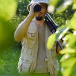Journey on safari tour: portrait of tourist or exploring scientist male in pith helmet having fun observing looking through scope  on summer sunny day green woods copy space background — Stock Photo #53101599