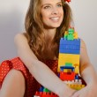 Portrait of beautiful funny young pinup girl with great dental whitening teeth smile in red polka dot dress having fun playing with toy constructor and looking up on light copy space background — Stock Photo #53103183